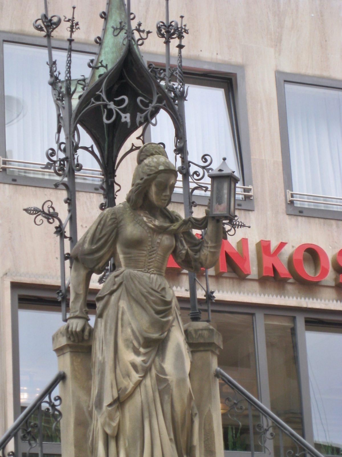 Die Schneidersfrau des Heinzelmännchen-Brunnen in Köln mit der Lampe in der Hand